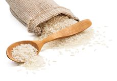 Sack and wooden spoon with scattered rice on white background Stock Images
