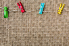 Sackcloth texture background with colorful wood clips Royalty Free Stock Image