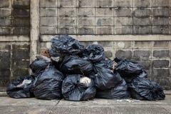 Sacken Sie Abfall auf Straße oder Bürgersteig mit alter Backsteinmauer ein lizenzfreies stockbild
