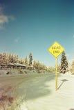 Sackgassezeichen neben der Straße wird mit Schnee umfasst Stockfotografie
