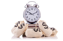 Sacks of money and alarm clock. On white Royalty Free Stock Photography
