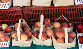 Sacks of Peaches at Local Fruit Market. Bags of peaches at a local farmers market for sale Royalty Free Stock Photos