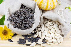 Sacks of sunflower and pumpkin seeds on the mat. Macro view of raw sunflower and pumpkin seeds in flax sacks with flower and pumpkin on the mat Royalty Free Stock Photo