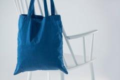 Saco azul que pendura em uma cadeira branca Imagens de Stock