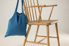 Saco azul que pendura em uma cadeira de madeira Fotos de Stock