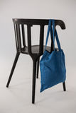Saco azul que pendura em uma cadeira preta Imagem de Stock Royalty Free