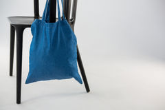 Saco azul que pendura em uma cadeira preta Imagens de Stock Royalty Free