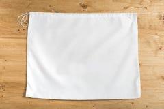 Saco branco do saco em cordas no fundo de madeira, trocista acima imagem de stock