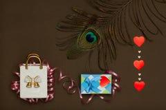 Saco cerâmico branco, caixa azul com o presente do dia de Valentim, pena do pavão e coração Foto de Stock