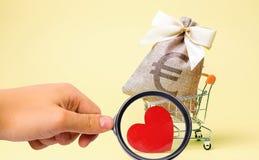 Saco com euro- sinal e coração vermelho em um trole do supermercado charity donation Ajuda social oferecer-se Dinheiro da economi fotos de stock royalty free