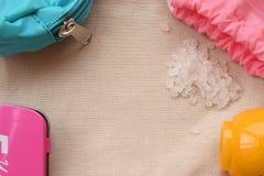 Saco cor-de-rosa, caixa magenta, sal do mar e frasco amarelo do creme no pano natural Fotos de Stock