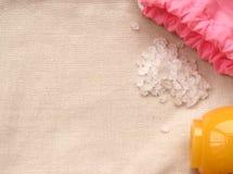 Saco cor-de-rosa, sal e frasco amarelo do creme no pano natural Foto de Stock Royalty Free