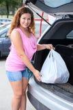 Saco da carga da cliente da mulher no tronco de seu suv Fotos de Stock