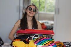 Saco da embalagem da menina para o curso, fechando o saco mal enchido em demasia da bagagem Foto de Stock