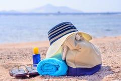 Saco da praia e chapéu de Sun em Sunny Deserted Beach foto de stock royalty free