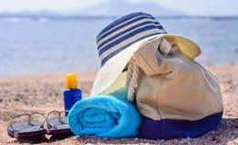 Saco da praia e chapéu de Sun em Sunny Deserted Beach fotos de stock royalty free
