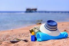 Saco da praia e chapéu de Sun em Sunny Deserted Beach foto de stock
