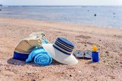 Saco da praia e chapéu de Sun em Sunny Deserted Beach imagem de stock royalty free