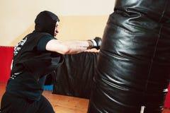 Saco de arena de derrota del boxeador en el gimnasio fotos de archivo libres de regalías