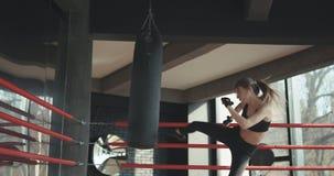 Saco de arena del entrenamiento de la mujer de Kickboxing en cuerpo feroz del ajuste de la fuerza del estudio de la aptitud almacen de metraje de vídeo