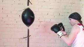 Saco de arena hermoso del entrenamiento de la mujer de Kickboxing en la serie apta 4k del kickboxer del cuerpo de la fuerza feroz almacen de metraje de vídeo