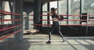 Saco de arena hermoso del entrenamiento de la mujer en cuerpo apto de la fuerza feroz del estudio de la aptitud metrajes