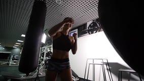 Saco de arena hermoso del entrenamiento de la mujer de Kickboxing en serie apta del kickboxer del cuerpo de la fuerza feroz del e almacen de metraje de vídeo