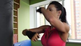 Saco de arena kickboxing atractivo del entrenamiento de la mujer de la raza mixta en fuerza feroz del estudio de la aptitud en la almacen de metraje de vídeo
