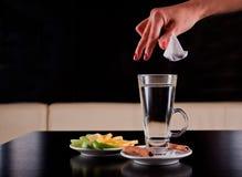 Saco de chá deixando cair da mão da mulher no vidro de água quente Foto de Stock