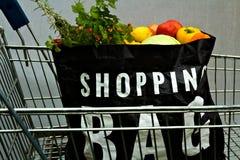 Saco de compras completo do supermercado do autosserviço na carta do trole fotos de stock