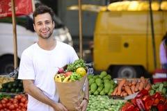Saco de compras levando do homem com alimento biológico. foto de stock