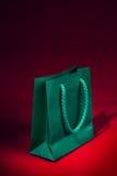 Saco de compras verde no vermelho Fotos de Stock Royalty Free
