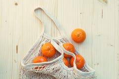 Saco de corda eco-amigável branco com frutos, laranjas no fundo de madeira, compra livre plástica foto de stock