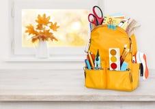 Saco de escola amarelo na tabela de madeira sobre o fundo da soleira do outono imagens de stock royalty free