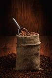 Saco de feijões e de colher de café Em um backgroundund de madeira Foto de Stock Royalty Free