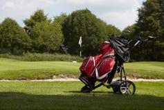 Saco de golfe com diversos clubes em um trole no fairway Imagens de Stock