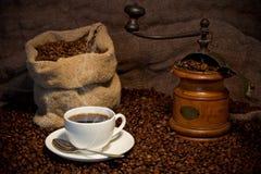Saco de granos de café, de taza blanca y de amoladora de café Foto de archivo