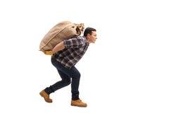 Saco de la arpillera del trabajador que lleva agrícola de sexo masculino en el suyo detrás imagen de archivo