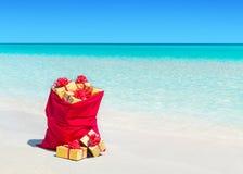 Saco de la Navidad por completo de cajas de regalo envueltas en la playa tropical Fotografía de archivo libre de regalías