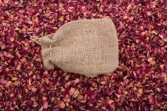 Saco de linho no fundo das pétalas cor-de-rosa secadas Imagens de Stock