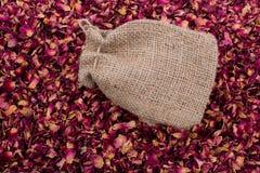 Saco de linho no fundo das pétalas cor-de-rosa secadas Fotos de Stock Royalty Free