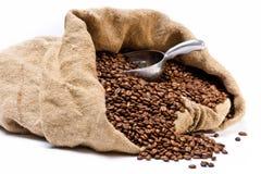 Saco de los granos de café con la cucharada del metal Foto de archivo libre de regalías