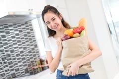 Saco de papel bonito asiático novo da compra da posse da menina com vegetais fotografia de stock royalty free