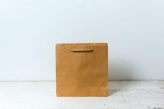 Saco de papel de Brown no fundo de madeira da tabela Fotografia de Stock Royalty Free