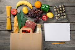 Saco de papel de produtos alimentares e de caderno com página vazia fotografia de stock royalty free