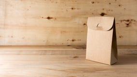 Saco de papel no fundo de madeira imagem de stock