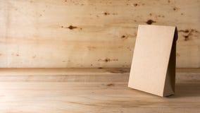 Saco de papel no fundo de madeira Imagens de Stock