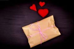 Saco de papel, presente, amarrado com linha cor-de-rosa em um fundo preto, cr Fotografia de Stock