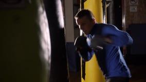 Saco de perfuração das batidas do pugilista O homem dos esportes bate um saco de perfuração O homem no gym O instrutor joga espor vídeos de arquivo