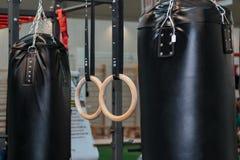 Saco de perfuração e anéis pretos da aptidão de Crossfit: Equipamento do exercício Fotos de Stock